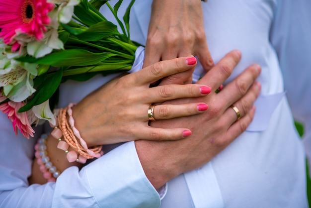 美しく洗練されたウェディングブーケのクローズアップは、新郎の隣に手で花嫁を保持します。ウェディングブーケとリング。