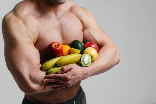明るい果物と白い空間でポーズスポーティなセクシーな男。ダイエット。健康的なダイエット。