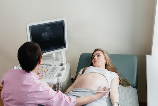 妊娠中の女の子が診療所で腹部の超音波検査を受けます。健康診断。