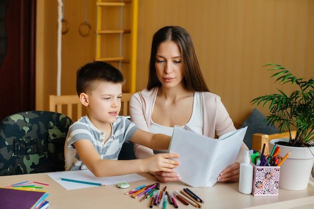 若い母親が息子の家で宿題をしています。両親とトレーニング。