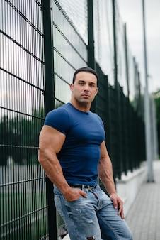 スポーツ男はスポーツフィールドの近くに立っています。ボディービル。