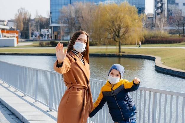 検疫とパンデミックの最中、晴れた日に若い家族が歩いて新鮮な空気を吸い込みます。人々の顔のマスク。