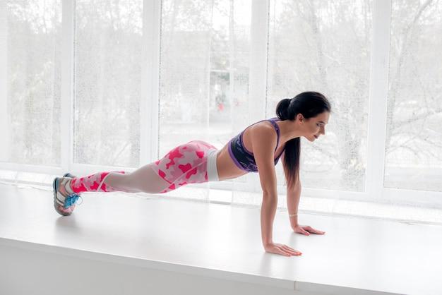 Спортивная (ый) молодая девушка выполняет упражнения в студии на светлом фоне. фитнес, здоровый образ жизни.