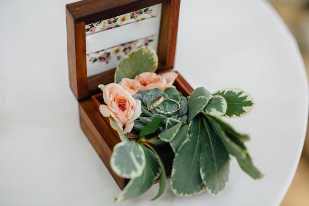 花嫁の集まりの間に、美しいボックスに結婚指輪をクローズアップ。アクセサリー。