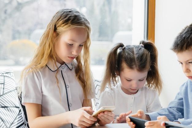 子供たちはカフェのテーブルに座って、一緒に携帯電話を遊びます。現代のエンターテイメント。