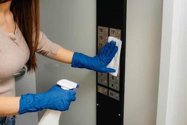 Молодая женщина дезинфицирует и чистит ключи в лифте во время глобальной пандемии. останься дома.