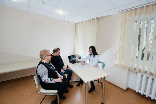 医療センターでかかりつけの医師の診察を受ける高齢者のカップル。医学とヘルスケア。