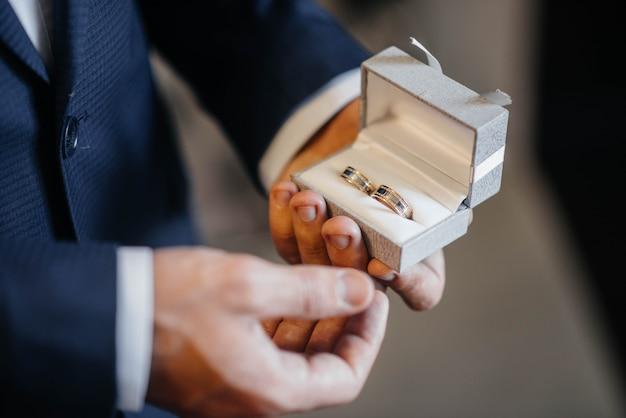 若い男が結婚指輪のクローズアップとボックスを保持しています。