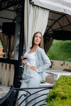 Красивая молодая девушка пьет вино на веранде красивого дома. праздничный день.