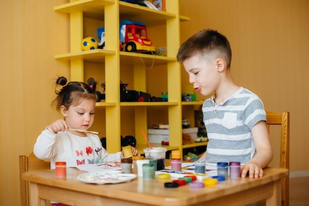 男の子と女の子が一緒に遊び、ペイントします。レクリエーションとエンターテイメント。家にいる。