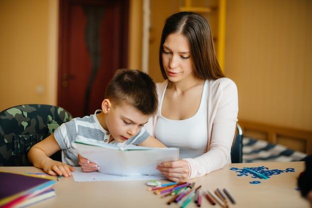 若い母親が息子と家で宿題をしている。両親とトレーニング。