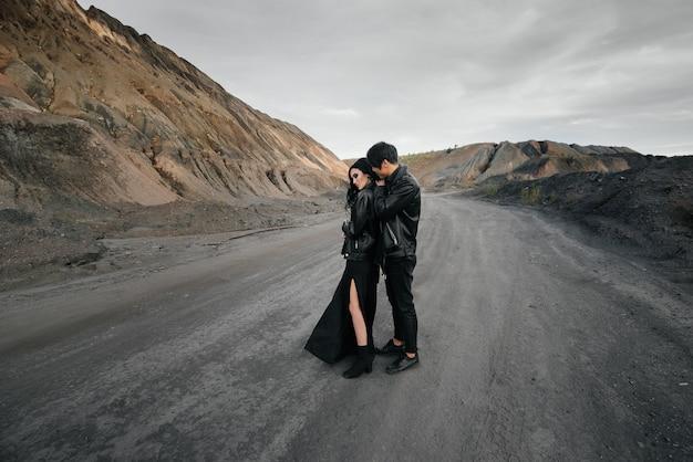 自然の中を歩く黒革の服に恋してアジアカップル。スタイル、ファッション、愛。