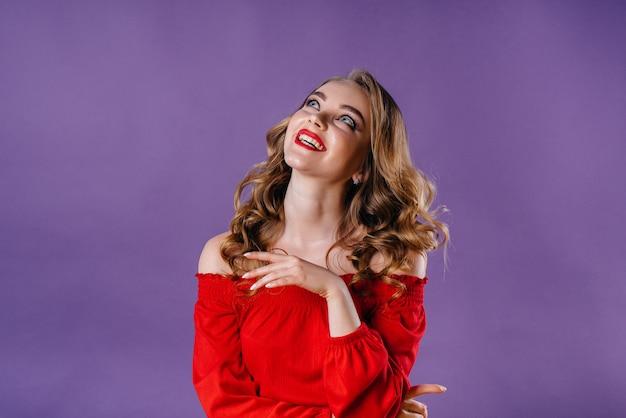 Молодая красивая девушка показывает эмоции и улыбки в студии на фиолетовом фоне. девушки для рекламы.