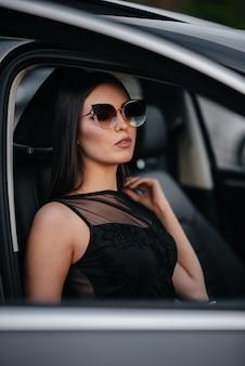 黒のドレスでビジネスクラスの車に座っているスタイリッシュな若い女の子。ビジネスのファッションとスタイル。