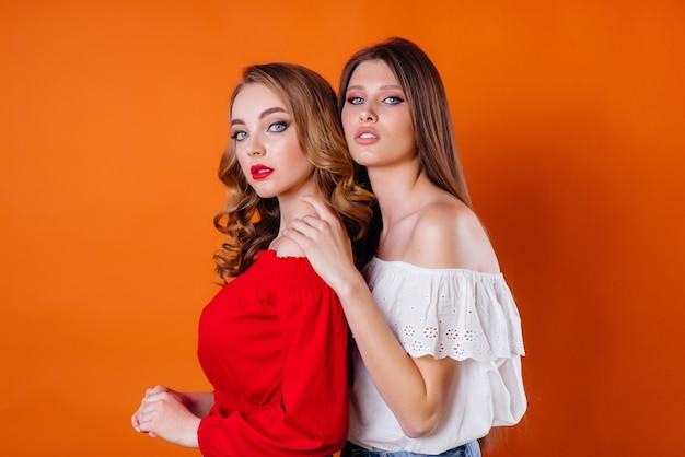 Две молодые и красивые девушки показывают эмоции и улыбки в студии на оранжевом фоне. девушки для рекламы.
