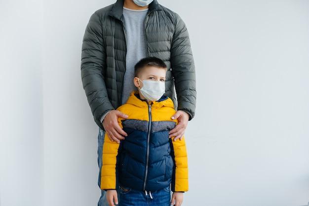 Отец с ребенком стоит в маске во время карантина. пандемия, коронавирус.