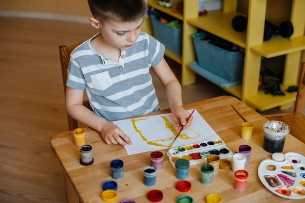 かわいい男の子が彼の部屋で遊んでいて絵を描いています。レクリエーションとエンターテイメント。家にいる。