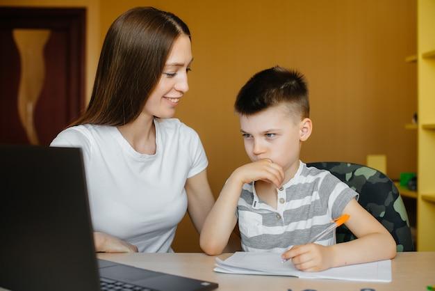母親と子供は自宅のコンピューターの前で遠隔学習に従事しています。家にいる、トレーニングする。