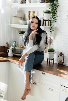 Красивая молодая девушка завтракает и пьет кофе на кухне. образ жизни.