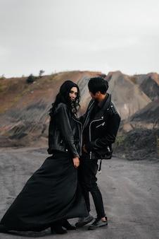 Азиатская влюбленная пара в черной кожаной одежде гуляет в природе среди деревьев. стиль, мода, любовь.