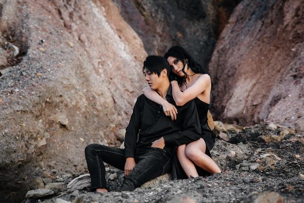 Азиатская пара в любви обнимает, сидя на скалах. любовная история.