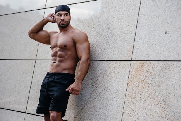 Сексуальный спортсмен стоит топлесс возле стены. фитнес, бодибилдинг.