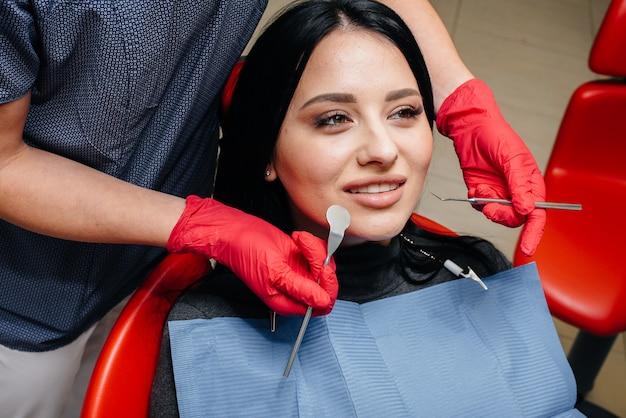 歯科医は患者の女の子の歯を治療します。歯科。閉じる。