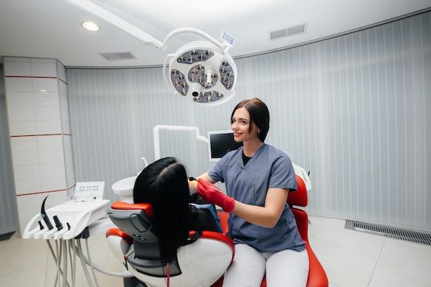 歯科医は患者の女の子の歯を治療します。歯科。