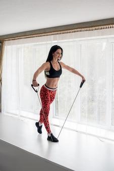 明るい背景にスタジオでフィットネスを行う運動の若い女の子。フィットネス、健康的なライフスタイル。