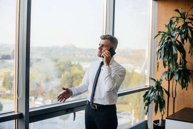Сотрудник в офисе стоит возле окна. финансы.