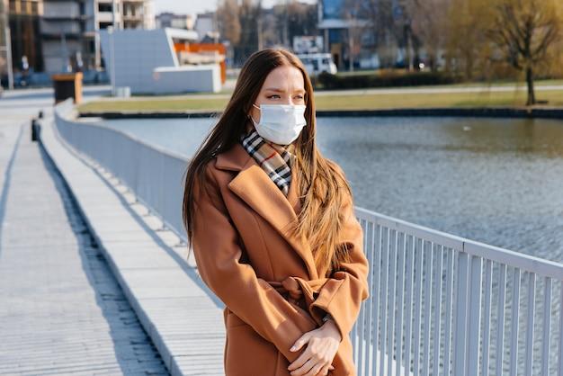 パンデミックとコロノウイルスの間、若い女の子がマスクの中を歩きます。検疫。