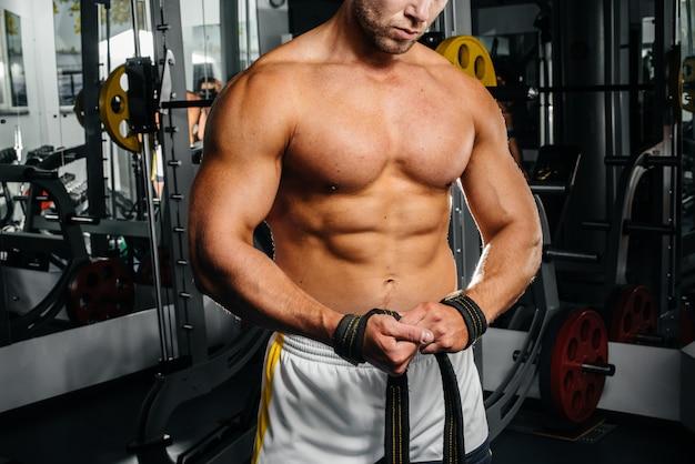 若い運動男はジムでフィットネスに従事しています。