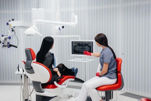 Стоматолог показывает картину зубов пациента и рассказывает о необходимом лечении