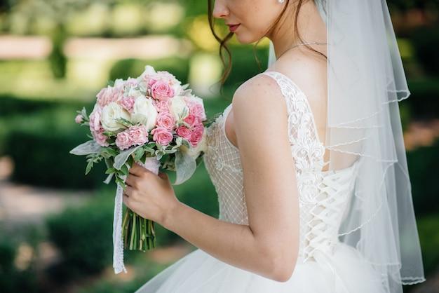 花嫁は彼女の手で美しい花束を保持しています。