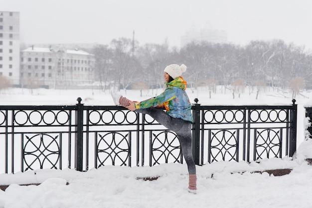 冷ややかな日に実行する前に、スポーツ少女がウォーミングアップします。フィットネス、ランニング。