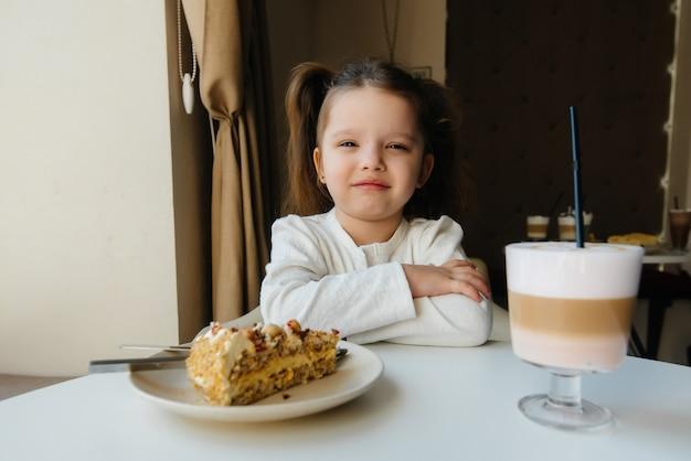 かわいい女の子がカフェに座って、ケーキとココアのクローズアップを見ています。食事と適切な栄養。