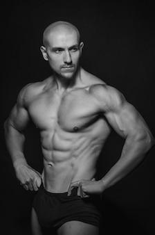 Спортивный парень позирует в студии на. спорт, красота, черно-белая фотография.