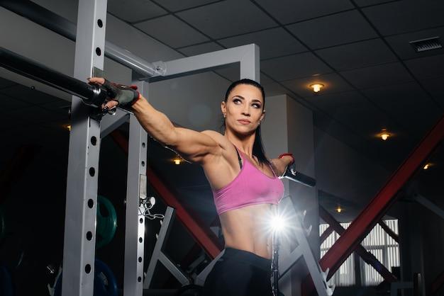 Спортивная молодая девушка позирует в тренажерном зале. занимаюсь спортом, фитнесом.