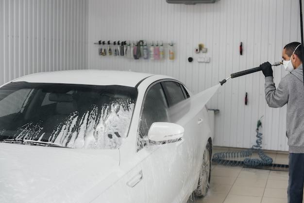 白い車の泡と高圧水による現代の洗浄。洗車。