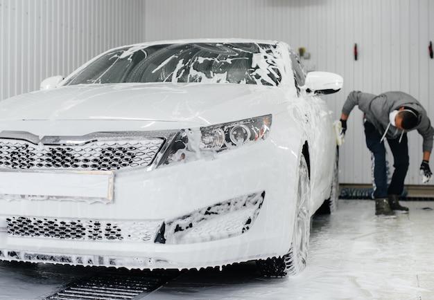 Современная стирка с пеной и водой под высоким давлением белого автомобиля. автомойка.