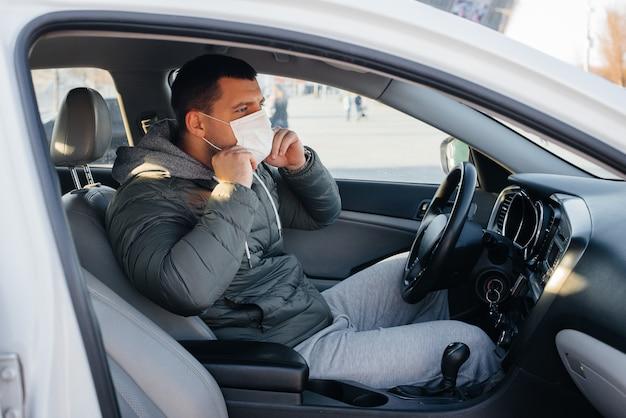 Молодой человек сидит за рулем в маске для личной безопасности во время вождения во время пандемии и коронавируса. эпидемия.