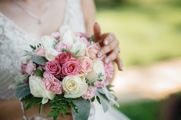 美しく洗練されたウェディングブーケのクローズアップは、花嫁を手に持っています。ウェディングブーケ。