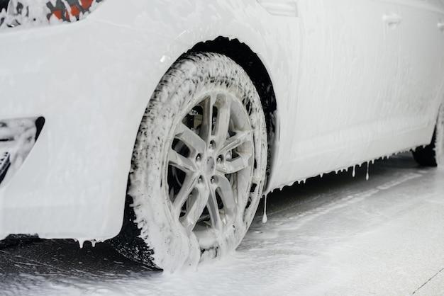 泡と高い水圧による車の車輪の現代的な洗浄。洗車。