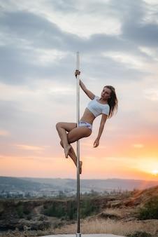 Молодая сексуальная девушка выполняет удивительные упражнения на шесте во время красивый закат. танцевать. сексуальность.