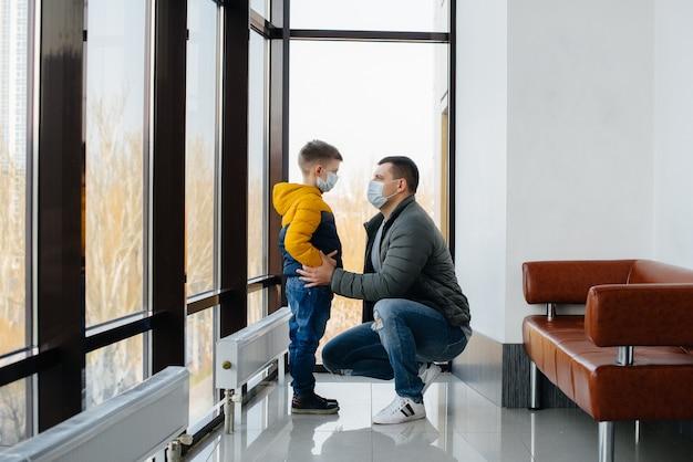 隔離中、子供を持つ父親が仮面に立っています。パンデミック、コロナウイルス。