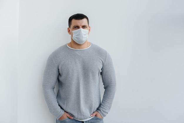 若い男性は、空きスペースのある検疫中にマスクをかぶった灰色の上に立っています。マスクの検疫。