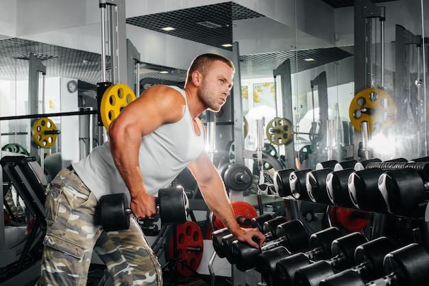 Молодой спортивный парень занимается фитнесом в тренажерном зале.