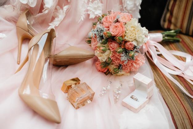 Обручальные кольца и другие аксессуары крупным планом во время сбора невесты. свадьба.