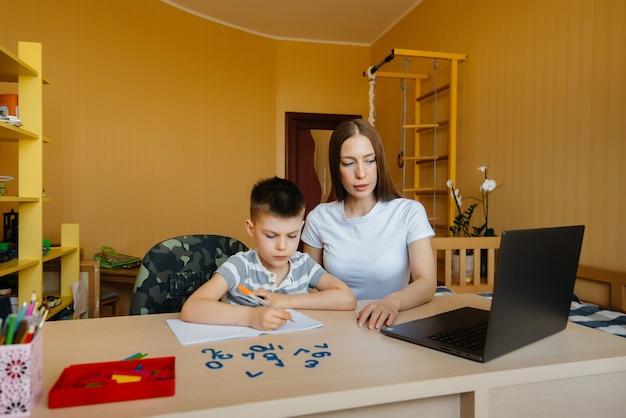 母親と子供は自宅のコンピューターの前で遠隔学習に従事しています。