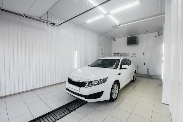 白い車の泡と高圧水による現代の洗浄。